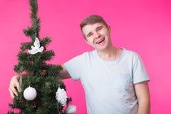 Άνθρωποι, διακοπές και έννοια Χριστουγέννων - νέο χαμογελώντας άτομο κοντά στο χριστουγεννιάτικο δέντρο στο ρόδινο υπόβαθρο στοκ φωτογραφίες με δικαίωμα ελεύθερης χρήσης