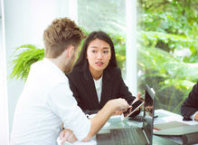άνθρωποι επιχειρησιακών ανδρών και γυναικών που κάνουν τη συνεδρίαση και που εξετάζουν την ταμπλέτα Στοκ Εικόνα