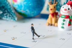 Άνθρωποι επιχειρησιακών μικροσκοπικοί αριθμών που περπατούν στο ημερολόγιο 31 ημερών και Στοκ Φωτογραφίες