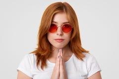 Άνθρωποι και έννοια πίστης Η θρησκευτική αρκετά νέα γυναίκα με τη σοβαρή έκφραση, κάνει τη χειρονομία επίκλησης, πιστεύει σε κάτι στοκ φωτογραφίες