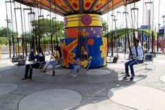 Άνθρωποι καρεκλών ταλάντευσης γύρου καρναβαλιού που απολαμβάνουν το γύρο καρναβαλιού στις καλοκαιρινές διακοπές Στοκ Φωτογραφίες