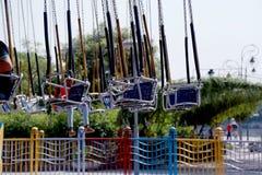 Άνθρωποι καρεκλών ταλάντευσης γύρου καρναβαλιού που απολαμβάνουν το γύρο καρναβαλιού στις καλοκαιρινές διακοπές Στοκ φωτογραφία με δικαίωμα ελεύθερης χρήσης