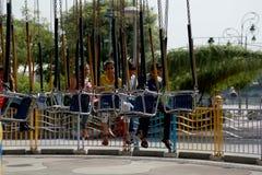 Άνθρωποι καρεκλών ταλάντευσης γύρου καρναβαλιού που απολαμβάνουν το γύρο καρναβαλιού στις καλοκαιρινές διακοπές Στοκ Εικόνα