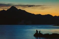 Άνθρωποι κοντά στον ποταμό και το βουνό το βράδυ στοκ εικόνες με δικαίωμα ελεύθερης χρήσης