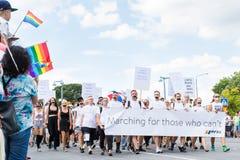 Άνθρωποι με τα δεμένα με ταινία στόματα που βαδίζουν με το έμβλημα κατά τη διάρκεια της παρέλασης υπερηφάνειας της Στοκχόλμης Στοκ φωτογραφίες με δικαίωμα ελεύθερης χρήσης