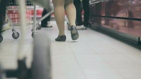 Άνθρωποι με τα καροτσάκια σε μια υπεραγορά που επιλέγει τα προϊόντα απόθεμα βίντεο