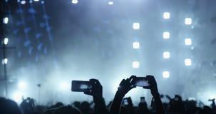 Άνθρωποι με τα κινητά τηλέφωνα σε μια συναυλία απόθεμα βίντεο