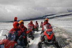 Άνθρωποι με το κόκκινα κράνος και το μαντίλι στο κόκκινο όχημα για το χιόνι που φορούν sungl Στοκ Εικόνες