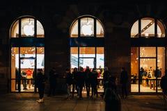Άνθρωποι μπροστά από την πρόσοψη της Apple Store τη νύχτα Στοκ Εικόνα