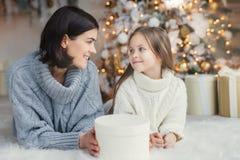 Άνθρωποι, οικογένεια, εορτασμός και έννοια διακοπών Η μητέρα και η κόρη με την ελκυστική εμφάνιση εξετάζουν η μια την άλλη μάτια  στοκ εικόνες
