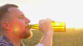 Άνθρωποι, ποτά και έννοια οινοπνεύματος - κλείστε επάνω της γενειοφόρου μπύρας κατανάλωσης νεαρών άνδρων από το μπουκάλι στην καυ φιλμ μικρού μήκους
