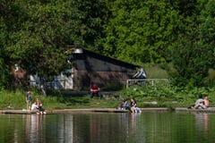 Άνθρωποι που έχουν έναν χρόνο διασκέδασης σε μια θερμή ημέρα κοντά στη λίμνη στοκ εικόνα με δικαίωμα ελεύθερης χρήσης