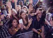 Άνθρωποι που έχουν τη διασκέδαση και που κάνουν τις φωτογραφίες σε μια συναυλία με το τρισδιάστατο κομφετί στοκ εικόνα