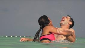 Άνθρωποι που έχουν τη διασκέδαση που κολυμπά στον ωκεανό φιλμ μικρού μήκους