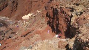 Άνθρωποι που έχουν το υπόλοιπο στην κόκκινη παραλία, βράχοι που βγήκαν μετά από την έκρηξη του ηφαιστείου απόθεμα βίντεο