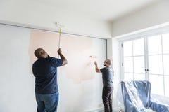 Άνθρωποι που ανακαινίζουν το σπίτι από κοινού στοκ φωτογραφία
