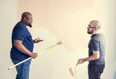 Άνθρωποι που ανακαινίζουν το σπίτι με τη ζωγραφική ενός τοίχου στοκ εικόνα
