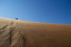 Άνθρωποι που αναρριχούνται κάτω από τον αμμόλοφο ερήμων στο αλατισμένο τηγάνι Sossusvlei Στοκ Φωτογραφίες