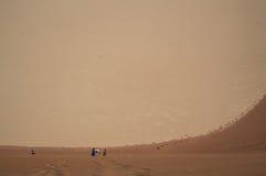 Άνθρωποι που αναρριχούνται κάτω από το μεγάλο αμμόλοφο μπαμπάδων στο αλατισμένο τηγάνι Sossusvlei Στοκ φωτογραφία με δικαίωμα ελεύθερης χρήσης