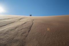 Άνθρωποι που αναρριχούνται κάτω από το μεγάλο αμμόλοφο μπαμπάδων στο αλατισμένο τηγάνι Sossusvlei Στοκ Εικόνες