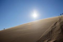 Άνθρωποι που αναρριχούνται πάνω-κάτω το μεγάλο αμμόλοφο μπαμπάδων, τοπίο ερήμων Στοκ φωτογραφία με δικαίωμα ελεύθερης χρήσης