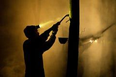Άνθρωποι που απασχολούνται στο apping λαστιχένιο δέντρο τη νύχτα Στοκ Φωτογραφία