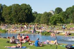 Άνθρωποι που απολαμβάνουν τη θερινή ημέρα στο πάρκο πόλεων Englischer Garten στο Μόναχο, Γερμανία Στοκ Εικόνες