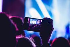 Άνθρωποι που απολαμβάνουν τη συναυλία βράχου και που παίρνουν τις φωτογραφίες με το τηλέφωνο α κυττάρων Στοκ φωτογραφίες με δικαίωμα ελεύθερης χρήσης