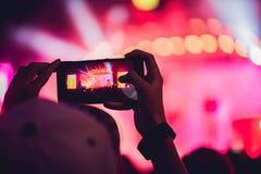 Άνθρωποι που απολαμβάνουν τη συναυλία βράχου και που παίρνουν τις φωτογραφίες με το τηλέφωνο α κυττάρων Στοκ Εικόνες