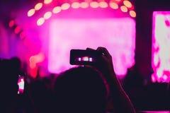 Άνθρωποι που απολαμβάνουν τη συναυλία βράχου και που παίρνουν τις φωτογραφίες με το τηλέφωνο α κυττάρων Στοκ εικόνα με δικαίωμα ελεύθερης χρήσης