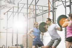 Άνθρωποι που βοηθούν το άτομο στην ανύψωση barbell στη γυμναστική crossfit στοκ φωτογραφία