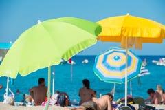Άνθρωποι που βρίσκονται κάτω από τις ζωηρόχρωμες ομπρέλες Στοκ Φωτογραφίες