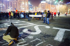 Άνθρωποι που γράφουν το μήνυμα στο σκυρόδεμα στη διαμαρτυρία, Βουκουρέστι, Ρουμανία στοκ εικόνα με δικαίωμα ελεύθερης χρήσης