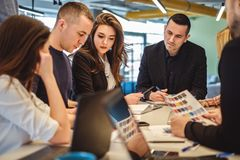 Άνθρωποι που εξετάζουν τη γραφική εργασία ενός συναδέλφου στη συνεδρίαση Στοκ Φωτογραφίες