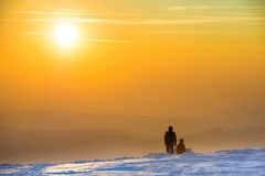 Άνθρωποι που εξετάζουν το ηλιοβασίλεμα στα χειμερινά βουνά Στοκ Φωτογραφία