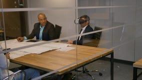 Συνεδρίαση επιχειρησιακών ομάδων σε έναν πίνακα, άτομο με τα προστατευτικά δίοπτρα εικονικής πραγματικότητας Άνθρωποι που εξετάζο απόθεμα βίντεο