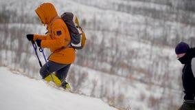 Άνθρωποι που επάνω μια κλίση που καλύπτεται με τη χλόη και το χιόνι φιλμ μικρού μήκους