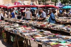 Άνθρωποι που επιλέγουν τα χρησιμοποιημένα βιβλία στην αγορά Aligre ψύλλων Παρίσι, Fra Στοκ Φωτογραφία