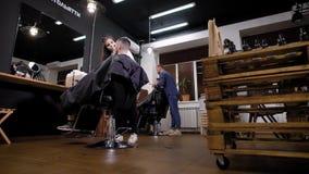Άνθρωποι που εργάζονται στην τρίχα των αρσενικών πελατών στο κατάστημα κουρέων φιλμ μικρού μήκους