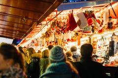 Άνθρωποι που θαυμάζουν τα δώρα Χριστουγέννων στο περίπτερο Στοκ Φωτογραφίες