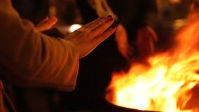 Άνθρωποι που θερμαίνουν τα χέρια κοντά στην πυρκαγιά στο φεστιβάλ οδών, εορτασμός χειμερινών διακοπών απόθεμα βίντεο