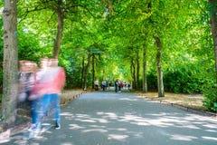 Άνθρωποι, που θολώνονται στην κίνηση, περπάτημα ήρεμο κατά μήκος του ελαφριού κτυπήματος πάρκων πόλεων Στοκ εικόνα με δικαίωμα ελεύθερης χρήσης
