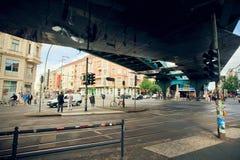 Άνθρωποι που διασχίζουν το δρόμο κάτω από το σταθμό u-Bahn γεφυρών undeground πλησίον Στοκ εικόνα με δικαίωμα ελεύθερης χρήσης