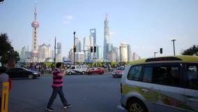 Άνθρωποι που διασχίζουν το δρόμο με το επιχειρησιακό κτήριο lujiazui της Σαγκάη απόθεμα βίντεο
