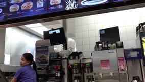 Άνθρωποι που διατάζουν τον καφέ στο μετρητή ελέγχων McDonalds απόθεμα βίντεο
