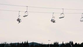 Άνθρωποι που κάνουν σκι και που στην κλίση χιονιού στο χειμερινό χιονοδρομικό κέντρο Ανελκυστήρας σκι στο βουνό χιονιού Χειμερινή φιλμ μικρού μήκους