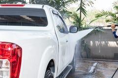Άνθρωποι που καθαρίζουν και που πλένουν αυτοκίνητο με το υψηλό πλυντήριο Στοκ Εικόνες
