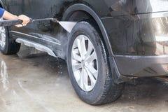 Άνθρωποι που καθαρίζουν και που πλένουν αυτοκίνητο με το υψηλό πλυντήριο (εστίαση Στοκ Φωτογραφία