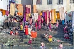 Άνθρωποι που καθαρίζουν τα ενδύματα και που πλένουν στον ποταμό Γάγκης σε Calcu Στοκ Φωτογραφίες