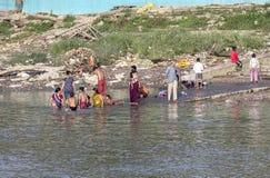 Άνθρωποι που καθαρίζουν τα ενδύματα και που πλένουν στον ποταμό Γάγκης σε Calcu Στοκ Εικόνες